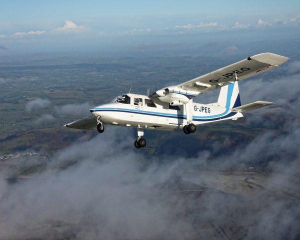 Survey aircraft over hills